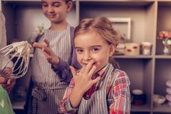 Cheerful pretty girl licking her fingers with cream royalty free stock photos