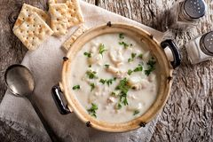 Creamy Fish Chowder. A delicious creamy white fish chowder with haddock, cod, potato, and onion garnished with parsley and served with soda crackers stock photo