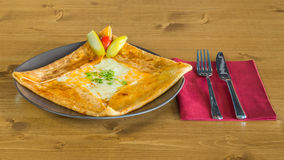 Delicious crepe with cheddar cheese and pickles beside served on a grey plate Royalty Free Stock Photos