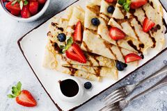 Delicious crepe with chocolate topping and fresh strawberry on white plate, top view