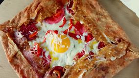Delicious crepe with egg, cheese and salami served with seasonings on a wooden board. Presentation of delicious crepe with egg, cheese and salami served with stock video