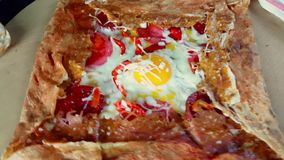 Delicious crepe with egg, cheese and salami served with seasonings on a wooden board. Presentation of delicious crepe with egg, cheese and salami served with stock video footage