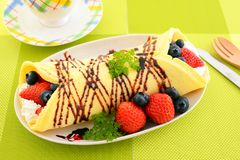 Delicious crepe. With fruits on the plate royalty free stock photos
