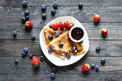 Delicious Crepes Breakfast with Dramatic light over a wood background. Startup Landing Webpage or Corporate Design Covers to use for web promotons, printed Stock Photography