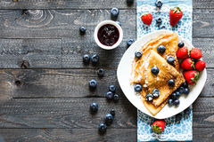 Delicious Crepes Breakfast with Dramatic light over a wood background. Delicious Crepes Breakfast with Dramatic light over a vintage wood background. An healthy Stock Photos