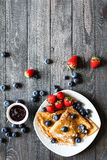 Delicious Crepes Breakfast with Dramatic light over a wood background. Delicious Crepes Breakfast with Dramatic light over a vintage wood background. An healthy Royalty Free Stock Photos