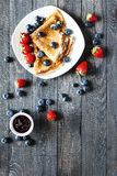 Delicious Crepes Breakfast with Dramatic light over a wood background Royalty Free Stock Photography