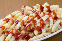 Delicious crinkle cut style french fries with ketchup Royalty Free Stock Image