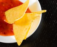 Delicious crisp corn nachos with spicy hot tomato sauce as a snack or appetizer in a white disc Royalty Free Stock Photography