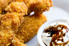 Delicious and Crispy Fried Chicken with Creamy Sauce. On a white plate food photography Royalty Free Stock Photography