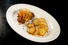 Delicious and Crispy Pork with Baked Potatoes and Decoration. On a white plate food photography Stock Images