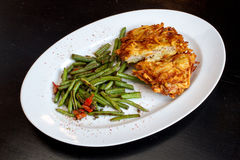 Delicious and Crispy Schnitzel with Green Beans. On white plate food photography Stock Images