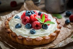 Delicious and crispy tart with berries and mascarpone. On baking paper stock images