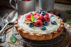Delicious and crispy tart with mascarpone cheese and fruit. On old wooden table stock image