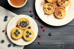 Delicious crispy tarts with custard cream. On plates Royalty Free Stock Photos