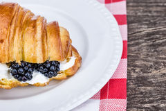Delicious croissant with cream and blueberries. Stock Photo