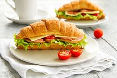 Delicious croissant sandwich on wooden table. Healthy breakfast. Delicious croissant sandwich with tomatos and salad on gray wooden table, Healthy breakfast in a stock photo