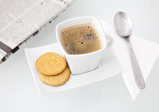 A delicious cup of coffee with biscuits. Spoon and with a newspaper, arranged for a perfect morning Royalty Free Stock Photos