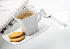 A delicious cup of coffee with biscuits. Spoon and with a newspaper, arranged for a perfect morning Stock Images