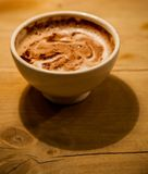Morning mocha. A delicious cup of coffee with chocolate sits on a unique wooden table Royalty Free Stock Image