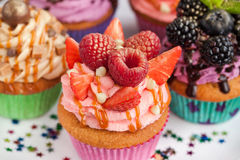 Delicious cupcake decorated with raspberry and strawberry. Delicious pink cupcake decorated with raspberry and strawberry Royalty Free Stock Photos
