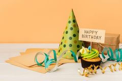 Delicious cupcake and gift on yellow background Royalty Free Stock Photos