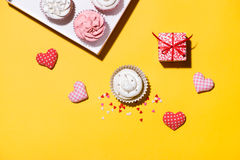 Delicious cupcake with paper box on yellow background Royalty Free Stock Photography