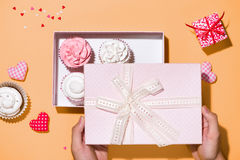 Delicious cupcake with paper box on yellow background Stock Images