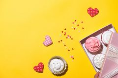 Delicious cupcake with paper box on yellow background Royalty Free Stock Image