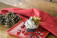 Delicious Cupcake with Red Accessories. An autumn themed chocolate cupcake with a brown fondant maple leaf garnish on a red dessert plate Royalty Free Stock Photos