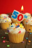 50th birthday. Delicious cupcake with 50th candle on top and 49 other cakes in background Royalty Free Stock Photo