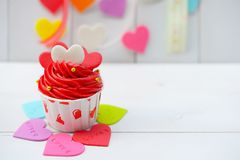 Cupcake with heart decoration on a white wooden background. Love and Valentine`s day concept Royalty Free Stock Images