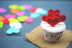 Cupcake with heart decoration on a white wooden background. Love and Valentine`s day concept Royalty Free Stock Photos
