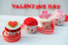 Cupcake with heart decoration on a white wooden background. Love and Valentine`s day concept Royalty Free Stock Photo