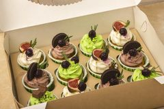 Delicious cupcakes in a box. Cupcakes with biscuits, figs, chocolate, marmalade. Royalty Free Stock Photos