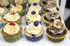 Delicious cupcakes with buttercream and fruits Royalty Free Stock Image