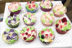 Delicious cupcakes with buttercream and fruits Stock Photography