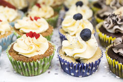 Delicious cupcakes with buttercream and fruits Royalty Free Stock Images