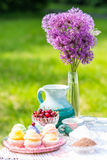 Delicious cupcakes, cherry and jug on the table in the garden. Cupcakes, cherry and jug on the table in the garden royalty free stock photo