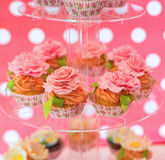Delicious cupcakes with cream roses on the glass plate Stock Images