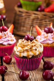 Delicious cupcakes decorated with caramel and fresh berries Royalty Free Stock Photography