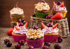 Delicious cupcakes decorated with caramel and fresh berries Royalty Free Stock Image