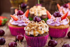 Delicious cupcakes decorated with caramel and fresh berries Stock Images