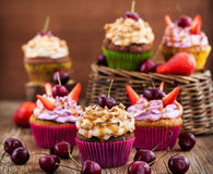 Delicious cupcakes decorated with caramel and fresh berries Royalty Free Stock Photos