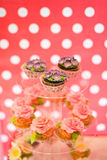 Delicious cupcakes and muffins with cream flowers on the glass plate Royalty Free Stock Photos