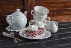 Delicious cupcakes and a tea set on a wooden table. Tea time. Stock Photography