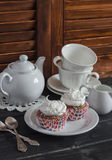 Delicious cupcakes and a tea set on a wooden table. Tea time. Stock Images