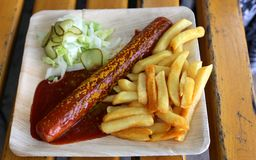 Currywurst curry sausage with french fries and cucumber salad and tomato ketchup. Delicious curry sausage with spices on elegant plate flat lay food fast food Royalty Free Stock Photos