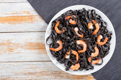 Delicious Cuttlefish ink pasta with prawns, top view. Delicious Cuttlefish ink black pasta with prawns on white dish on dark table mat on old peeling paint Royalty Free Stock Photo