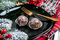 Delicious dark chocolate cakes covered with glazed. Tasty dessert food in close up. Chocolate desserts served on black plate, stock images